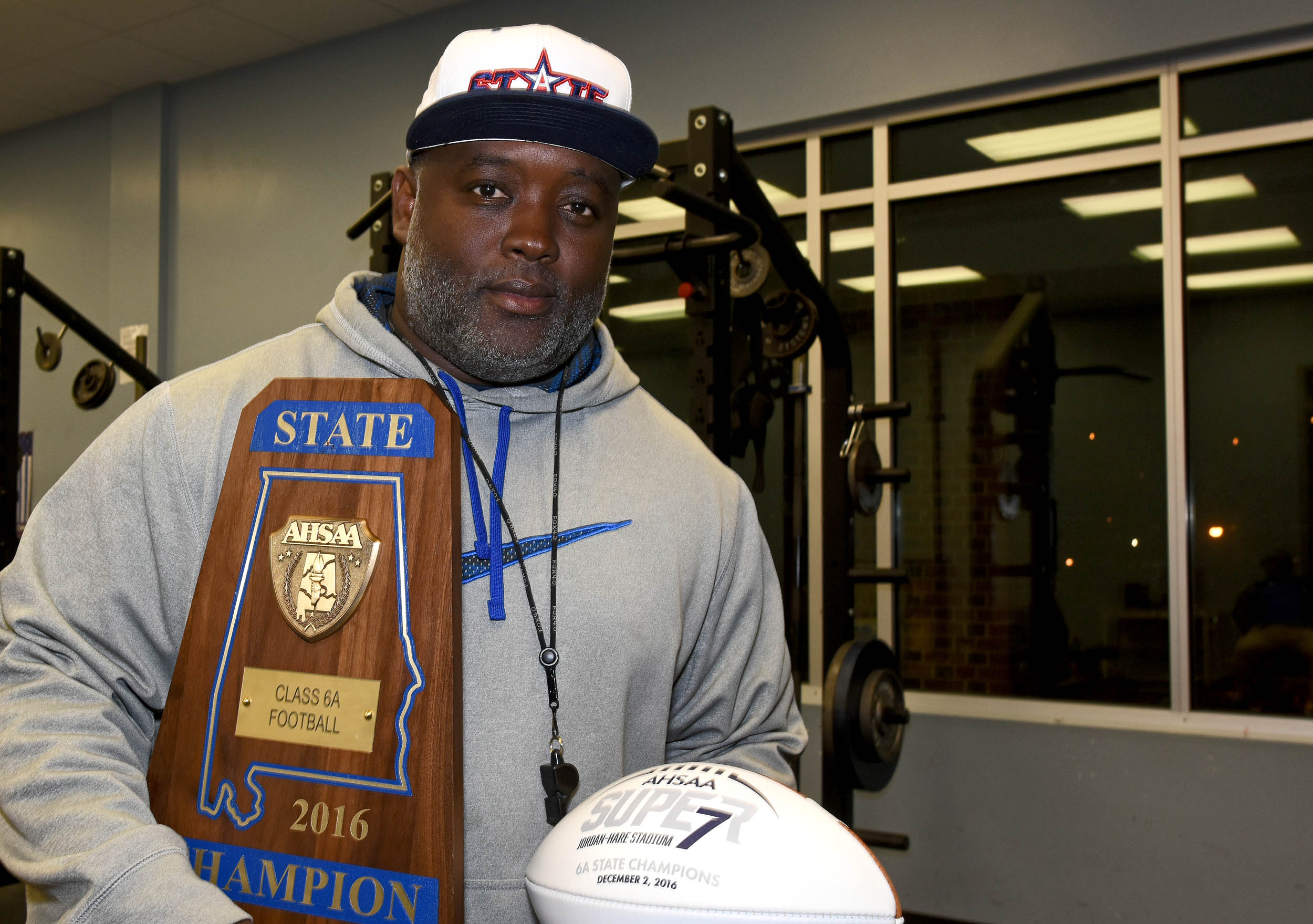 Coach Rueben Nelson Jr. cradles the championship trophy and football he received after his Ramsay Rams defeated Opelika 21-16 in Jordan-Hare Stadium  to win the Class 6A Alabama High School Athletic Association state football championship on Friday, Dec. 2, 2016.