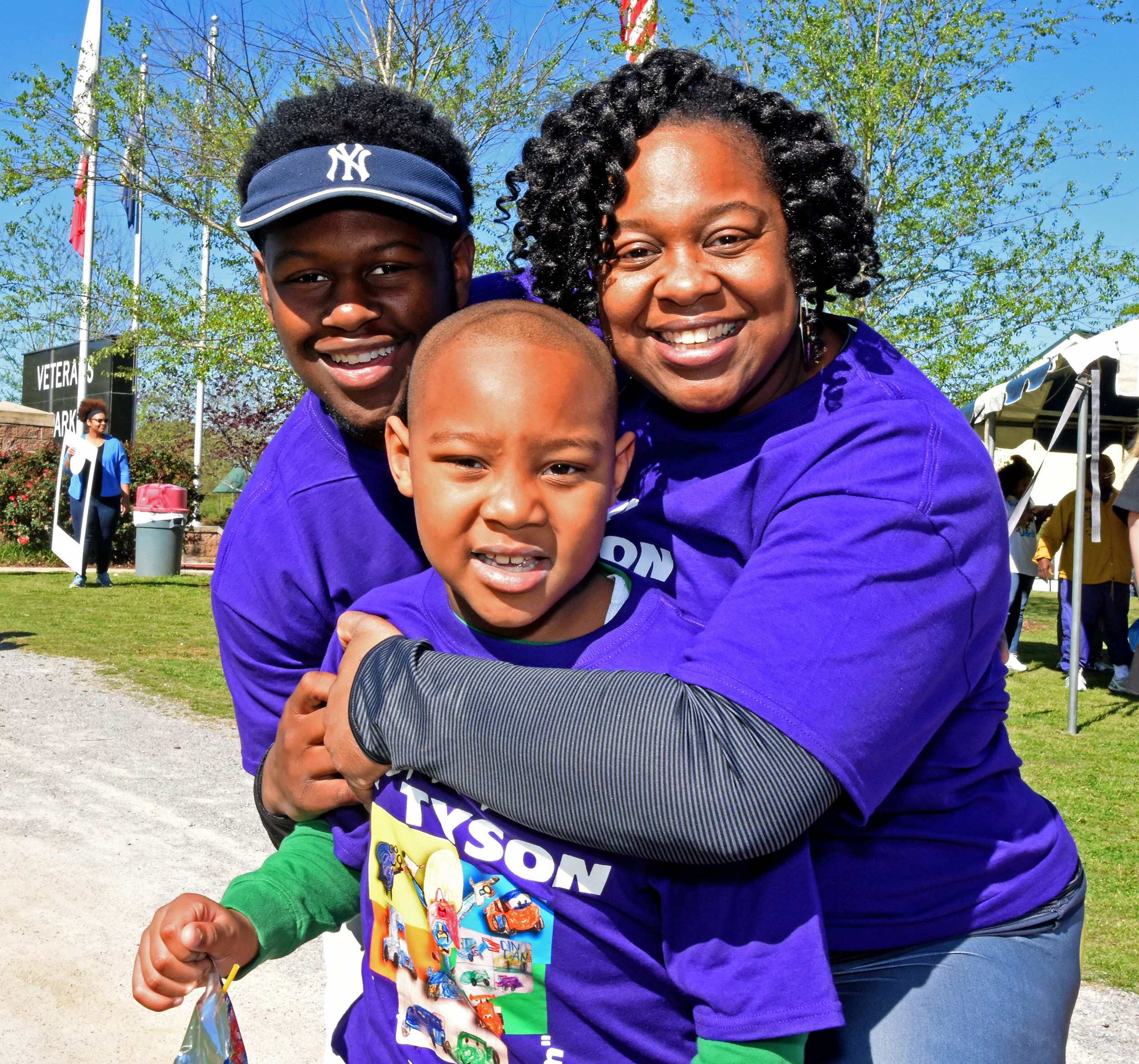 Tami Tyler, right, hugs her sons -- 16-year-old Dalen Tyler and 6-year-old Ethan Tyson Tyler -- at the Walk for Autism at Veterans Park in Hoover. Her younger son is autistic.