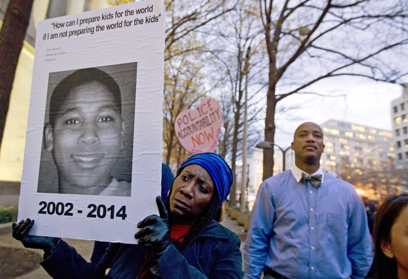 FILE – In this Dec. 1, 2014, file photo, Tomiko Shine, left, holds a sign with a photo of Tamir Rice, a boy fatally shot by a Cleveland police officer, while protesting a grand jury's decision in Ferguson, Mo., not to indict police officer Darren Wilson in the shooting death of Michael Brown, during a demonstration in Washington. Cleveland Police Chief Calvin Williams announced Tuesday, May 30, 2017, that Timothy Loehmann, the police officer who shot and killed the 12-year-old boy, has been fired for inaccuracies on his job application, while the officer who drove the patrol car the day of the Nov. 22, 2014, shooting, Frank Garmback, has been suspended for 10 days for violating a tactical rule for his driving that day. (AP Photo/Jose Luis Magana, File)