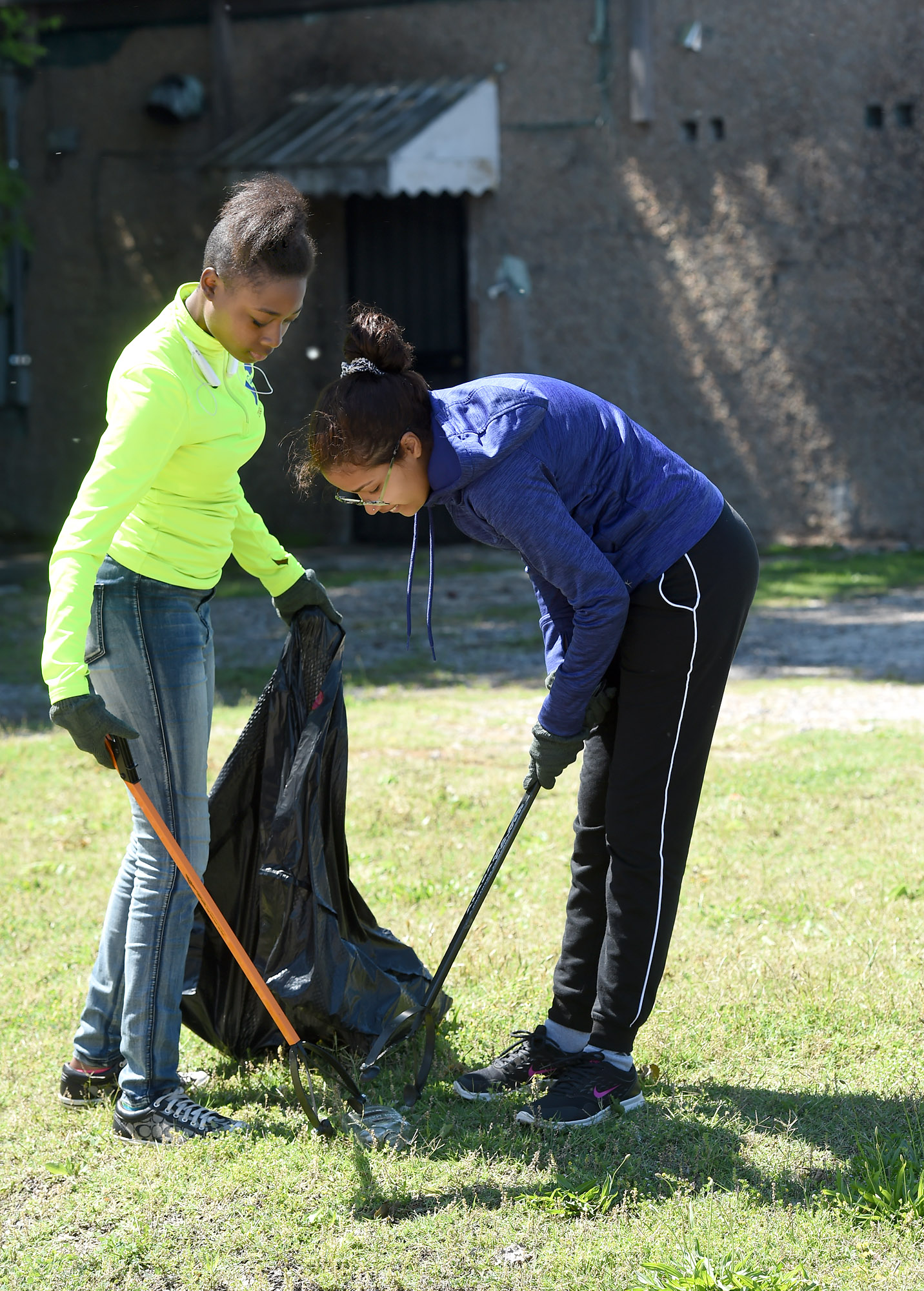 G.W. Carver High School students Clara Alameiva (right) and Latavia Walker pick up trash in the downtown Ensley area of Birmingham, Ala., Saturday, May 6, 2017. (Photo by Mark Almond)